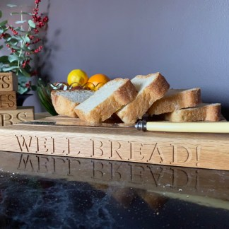 solid oak bread board with well bread engraved along the front edge