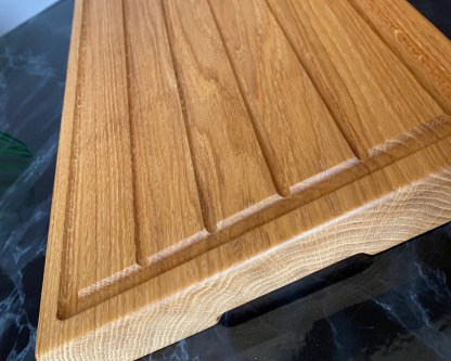 grooves on the underside of a solid oak carving board designed to facilitate lifting