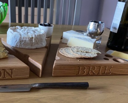 solid oak cheese board in the shape of a wedge with various holes along the edges and the surface designed to look like a piece of cheese. engraved with brie along the front edge