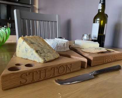3 solid oak cheese boards each in the shape of a wedge with various holes along the edges and the surface designed to look like a piece of cheese. each board engraved with a different cheese variety