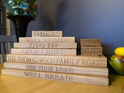 collection of solid oak chopping boards each one engraved with a different inscription along the front edge