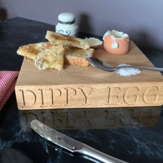 slateandoak solid oak block for toast and boiled eggs, with a hole in the top right designed as an egg cup. engraved along the front edge with dippy egg, personalised oak gifts