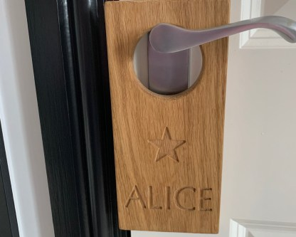 solid oak plaque engraved with a christian name and a star image, with a large hole designed to fit over a door handle denoting the name of the room or who it belongs to