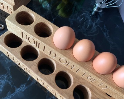 solid oak egg rack engraved along the front edge with boiled or fried or eggs-crack on