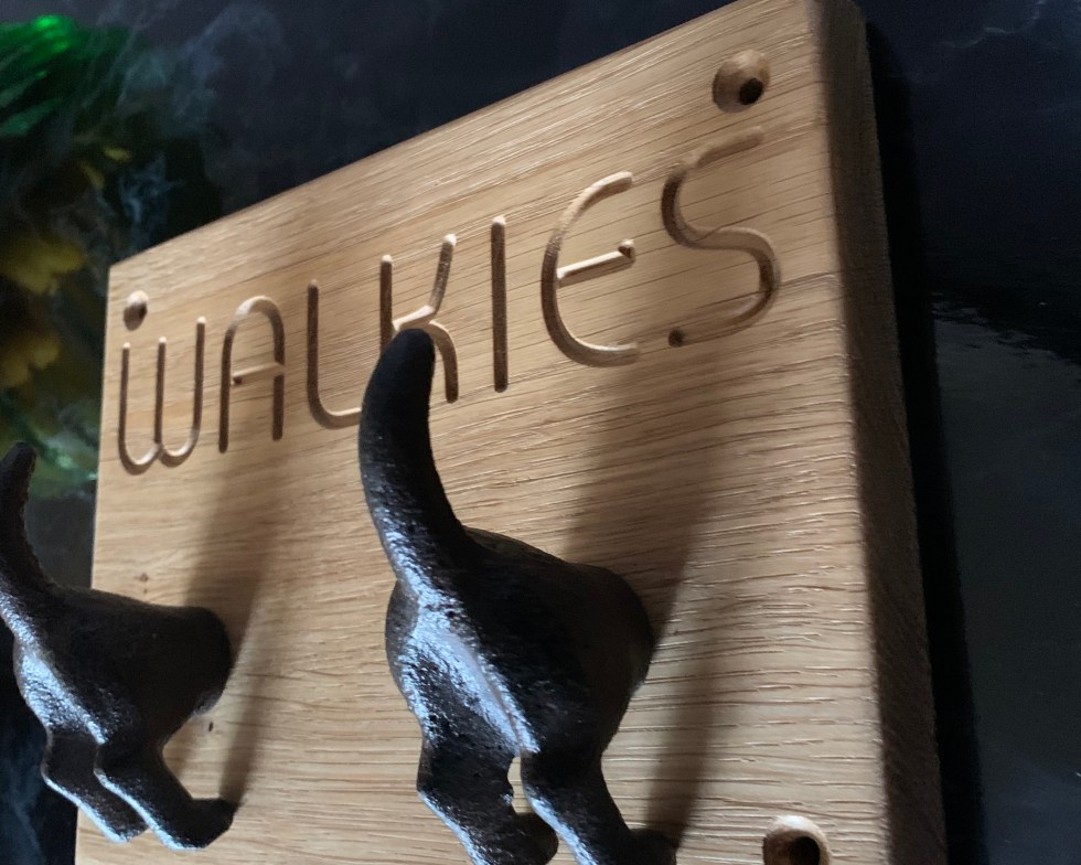 solid oak plaque engraved with walkies and fitted with two cast iron dog's bottoms for hanging up leads or coats