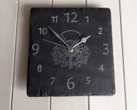 square welsh grey slate wall hanging clock with engraved numbers and an engraved thistle image in the middle