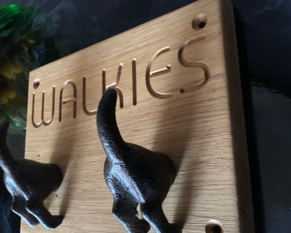 solid oak plaque engraved with walkies and fitted with 2 cast iron dog's bottoms for hanging up dog leads and coats