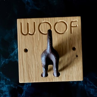 solid oak plaque engraved with WOOF and fitted with a cast iron dog's bottom designed to hang up leads or coats