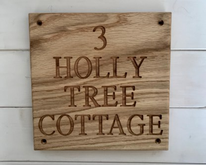 square solid oak house sign with 4 lines of engraved text, a mix of letters and numbers