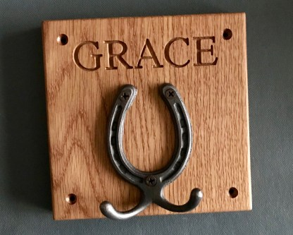 solid oak plaque engraved with a name and fitted with a small horseshoe which has two robe hooks attached. designed to be wall mounted