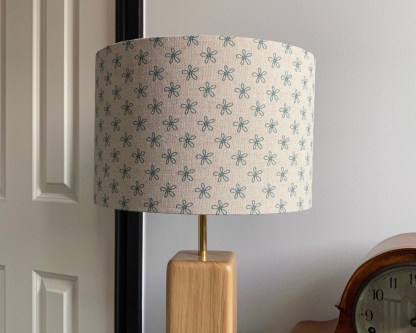 natural linen base with a teal blue print of daisy flowers made into a drum lampshade
