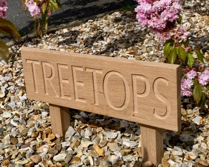 solid oak ground fixed low level house sign. an oak board engraved with the house name attached to two oak posts