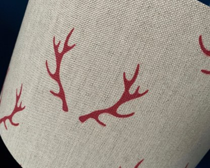 close up of natural linen fabric printed with a pair of red coloured antlers arranged in a step repeat pattern