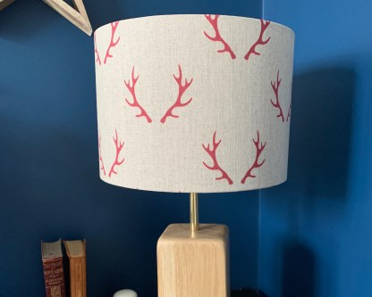 drum lampshade in natural linen fabric digitally printed with a pair of red coloured antlers arranged in a step repeat pattern