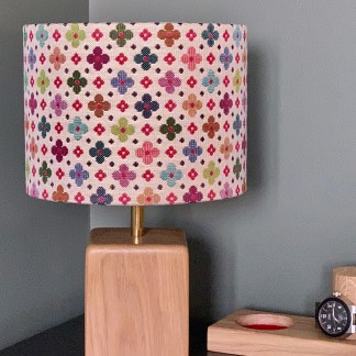 drum lampshade in tapestry style fabric with a daisy flower design on a cream background
