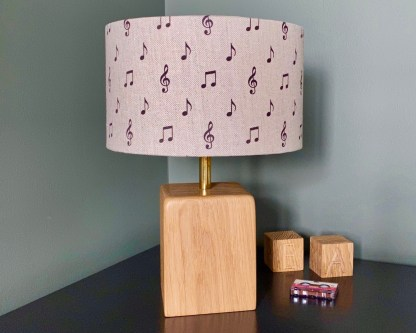 drum style lampshade made using natural linen fabric digitally printed with charcoal coloured musical notes in a cascading step design