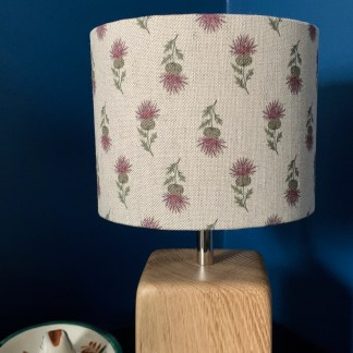 handmade drum lampshade using natural linen printed with a thistle design, fitted to a solid oak lampbase with chrome upriser