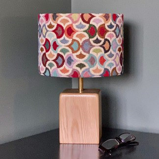 handmade lampshade in a tapestry style fabric with a wave design. fitted to a solid oak lamp base with brass up riser