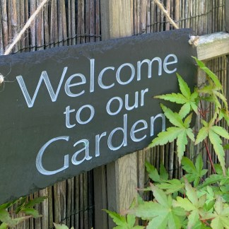 close up view of a hand cut welsh grey slate outdoor sign engraved with welcome to our garden. slateandoak