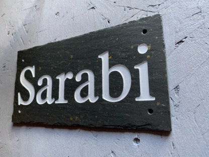 angled view of engraved slate stable sign showing a close up of the engraving and painting of the text