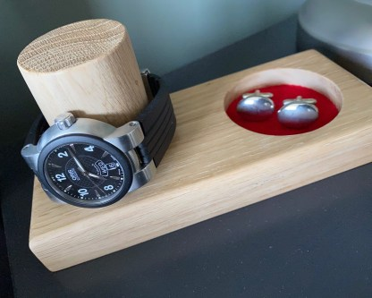 solid oak watch and cufflink or jewellery tray showing a watch placed over the vertical post and cufflinks in the tray