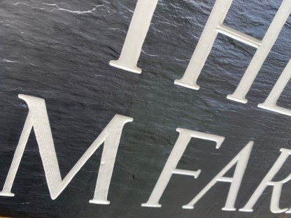 close up view of text on an engraved slate house sign with painted text and matt sealer