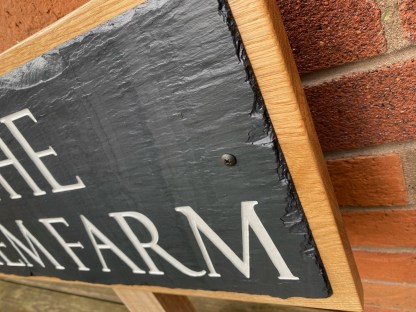 side view of a slate and oak wall or post mounted house sign. detailing the hand cut edge on the slate and the deep carved inscription which has been painted then finished with a matt sealer