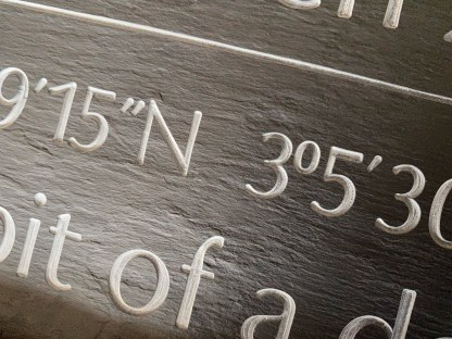 close up shot of engraved welsh grey slate with wedding venue gps coordinates