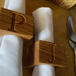 side angle view of oak napkin rings engraved with an initial