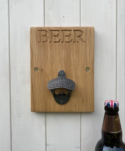 solid oak plaque engraved with the word beer and fitted with a cast iron bottle opener