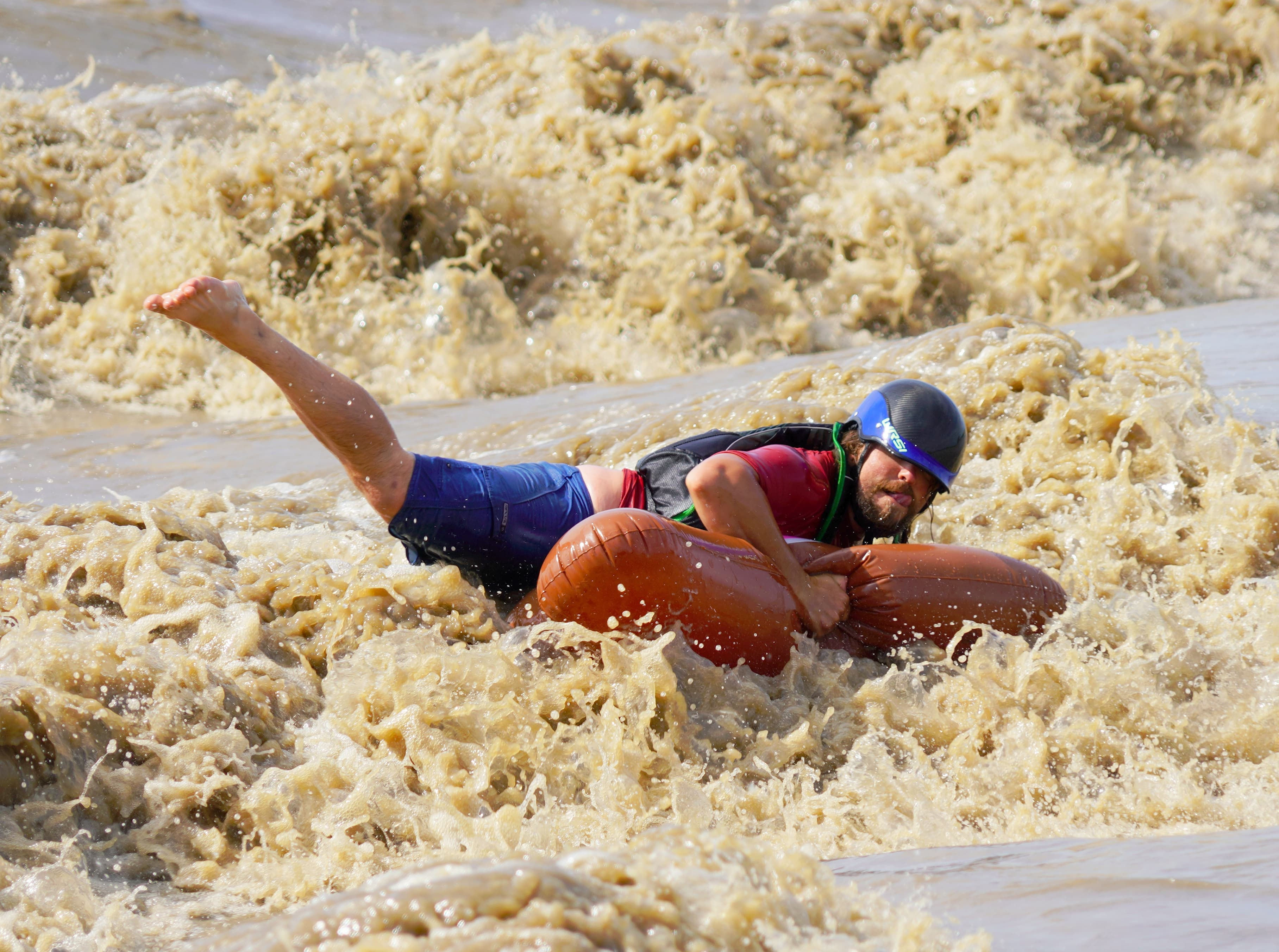 A person is body surfing on an inflatable pool toy.