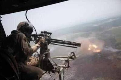 Door Gunner Fires From a Huey Helicopter