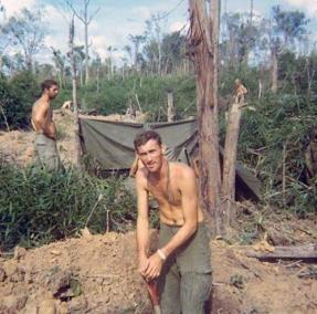 Soldier Digs a Foxhole in a Jungle Camp