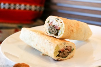 Kafta. Beef and parsley skewers, with grilled onions, tomatoes, pickles, and hummus