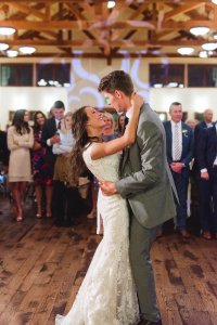 bride and groom dancing together on wood dancefloor with guests in background