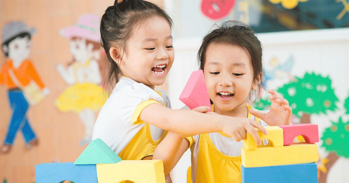 Two girls stacking blocks