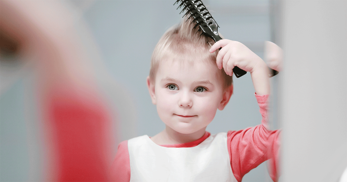 Small child brushing his hair and being self-sufficient.