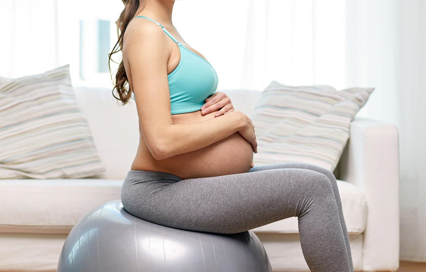 Twin pregnant mom holding her belly sitting on a yoga ball