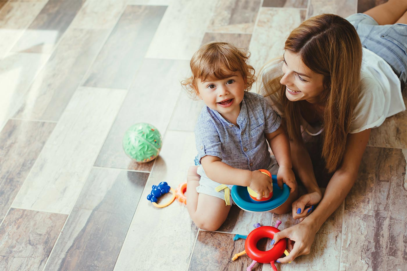 Mom and little boy playing with toys on the floor