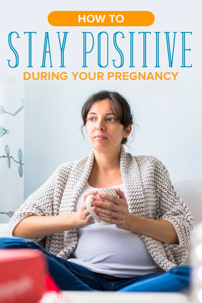 Despondent woman holding a mug, thinking about how to stay positive during pregnancy