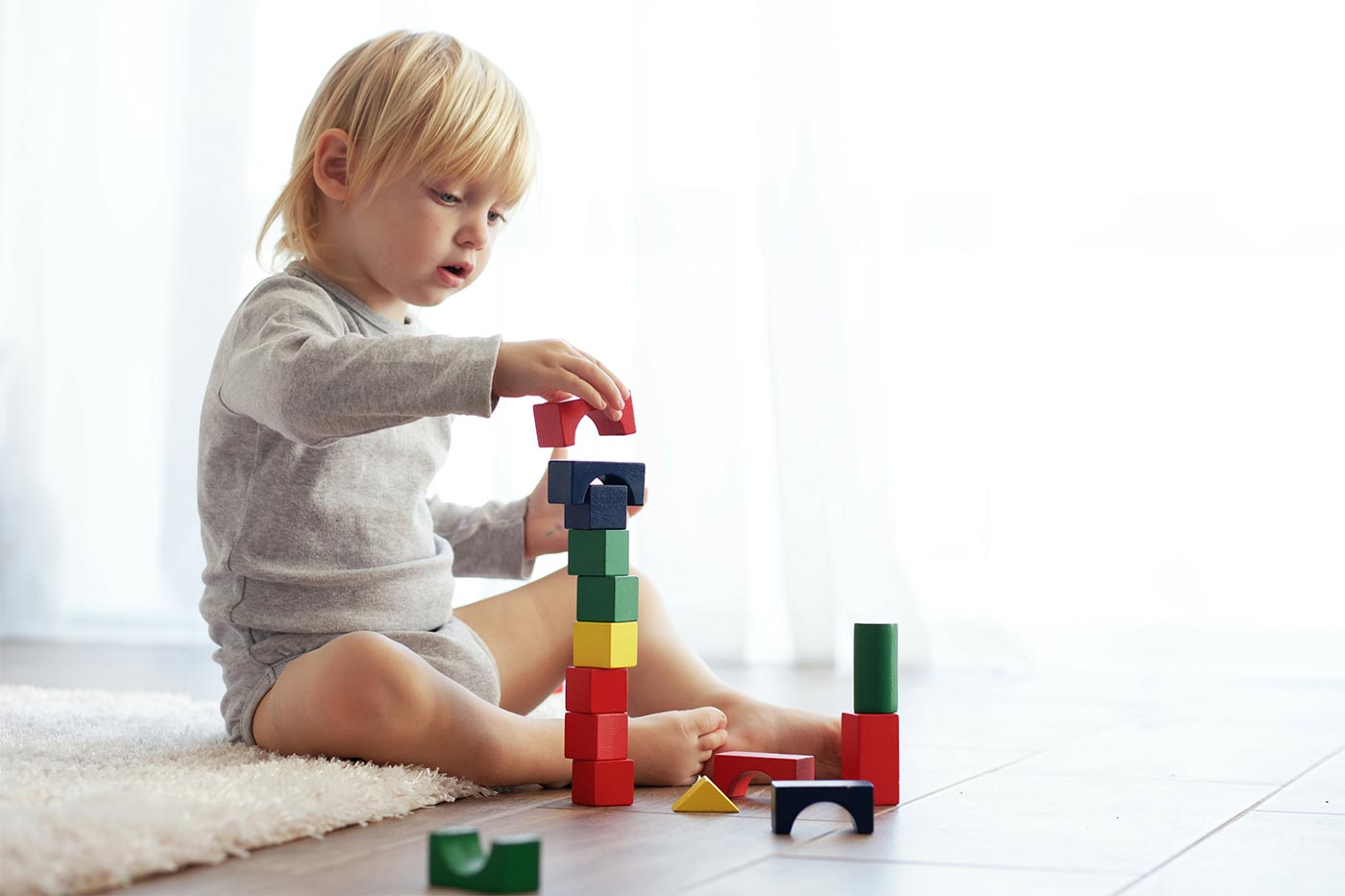 Child stacking wooden blocks