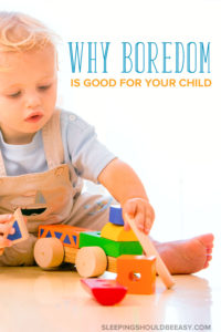 Little boy playing with a wooden train set