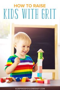 Little boy proud of building a tower of bricks: How to raise kids with grit
