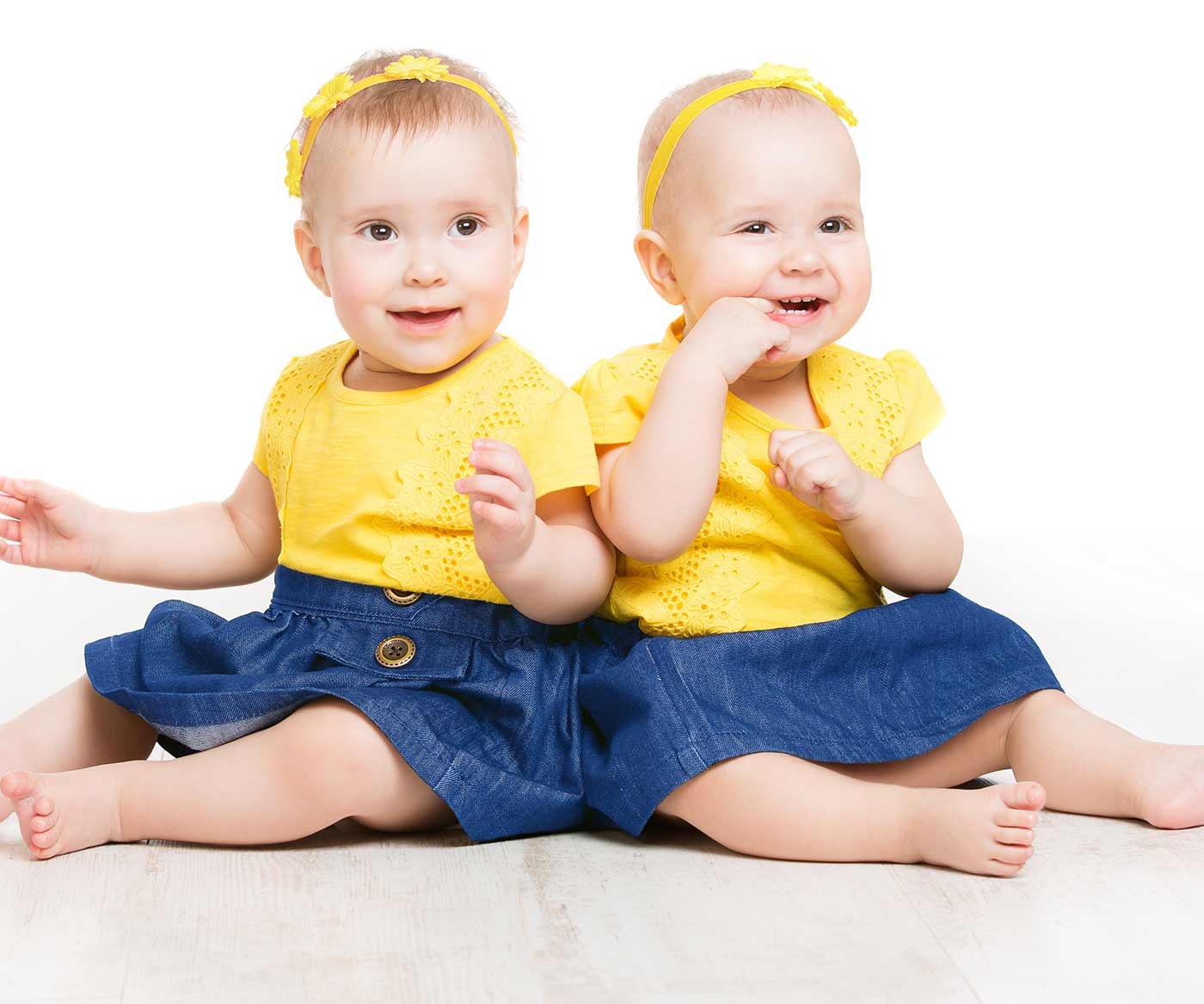 twin girls sitting and smiling: how to avoid excluding your non twin child