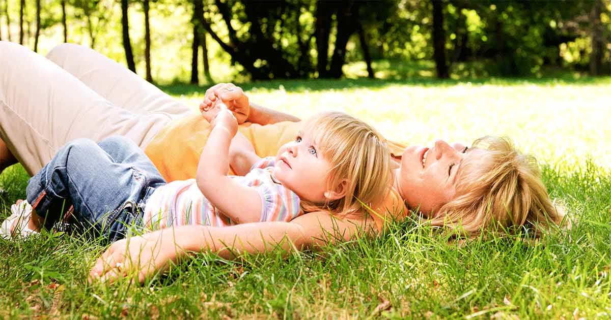 Mom and her daughter lying down on the grass, talking about emotions