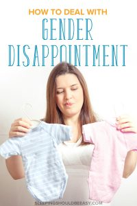Pregnant woman dealing with gender disappointment, holding up blue and pink onesies