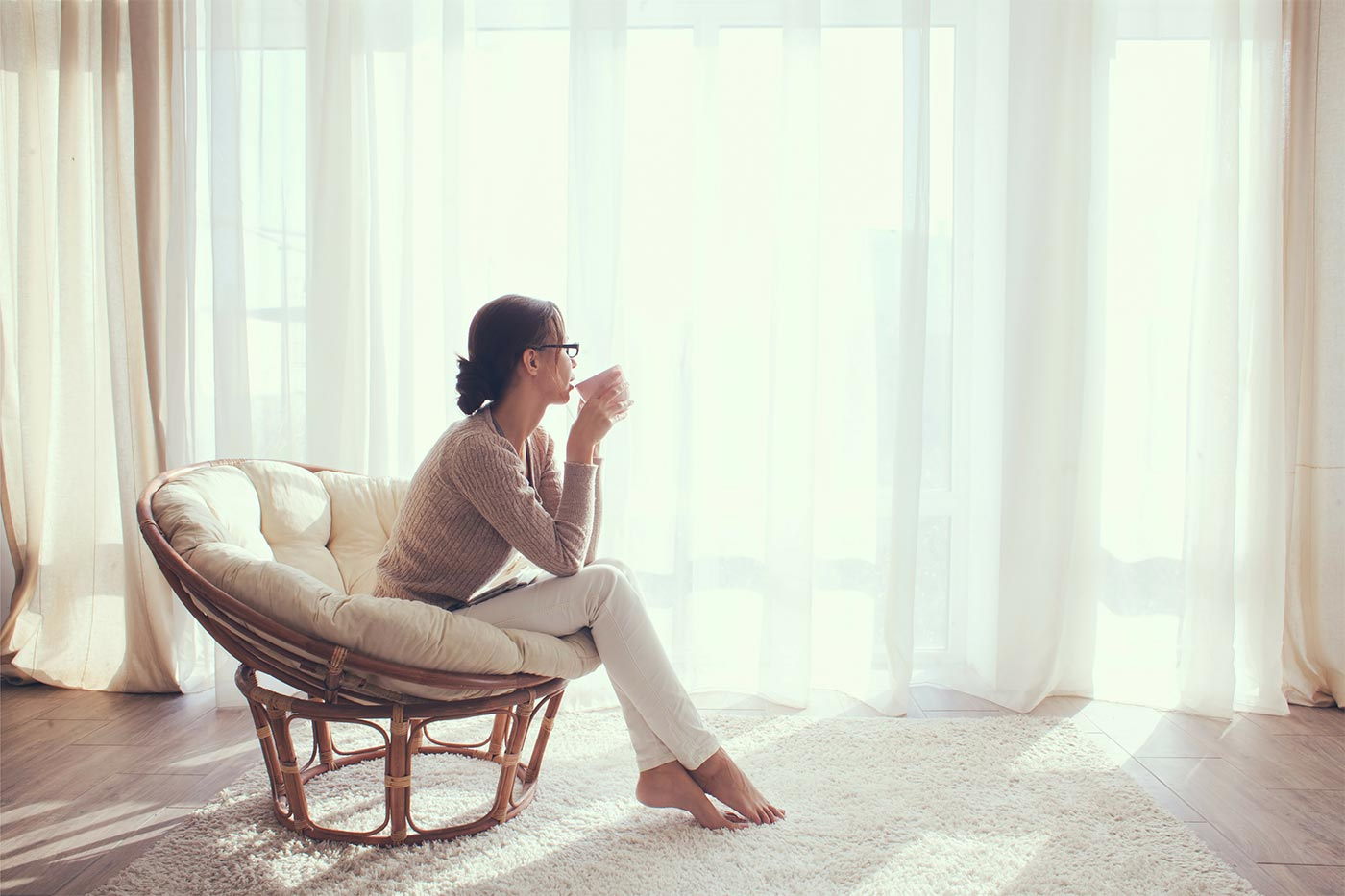 Woman sitting on a cushioned chair, sipping from a cup and looking out a window