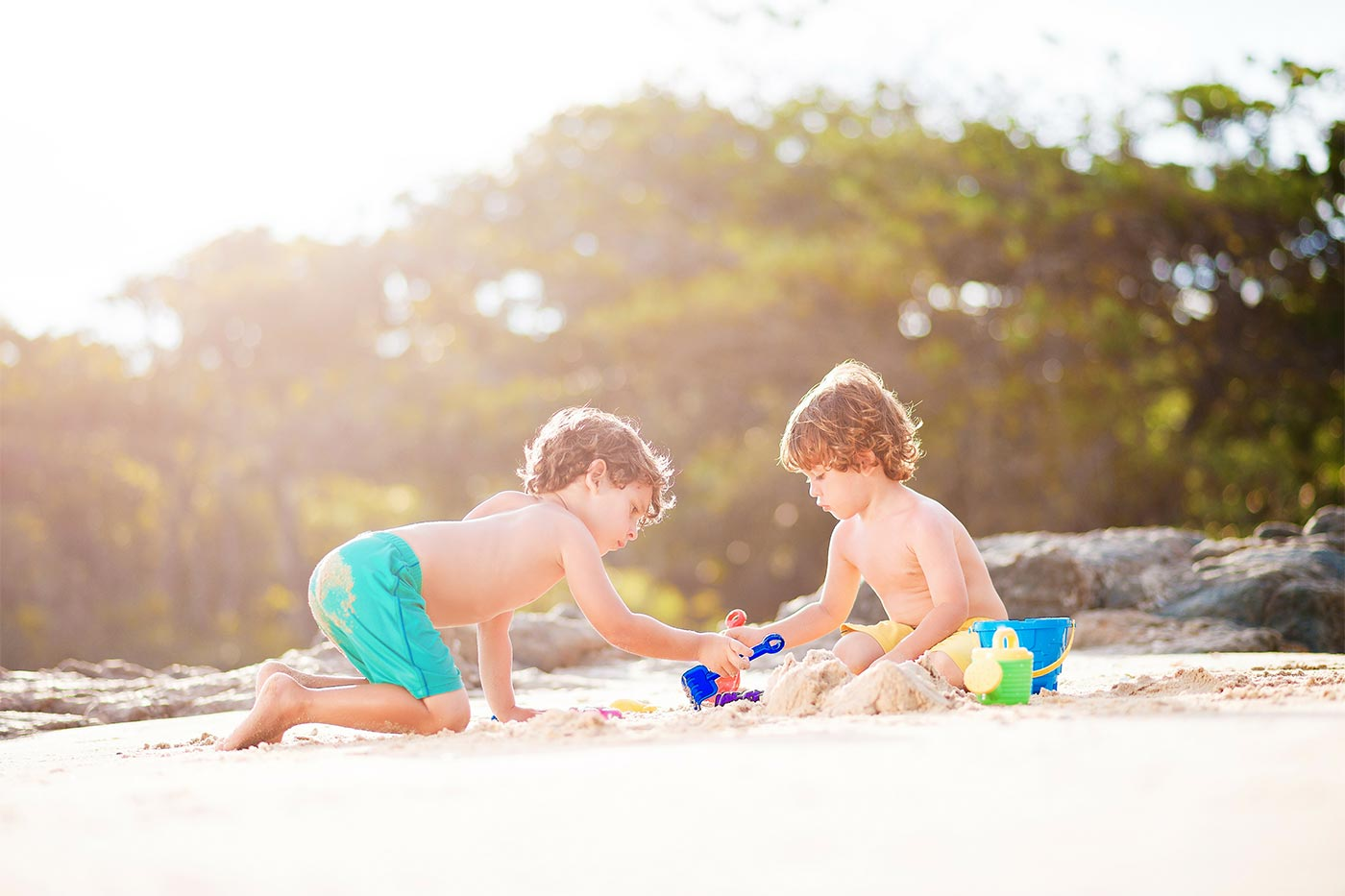 Brothers sharing toys on a beach