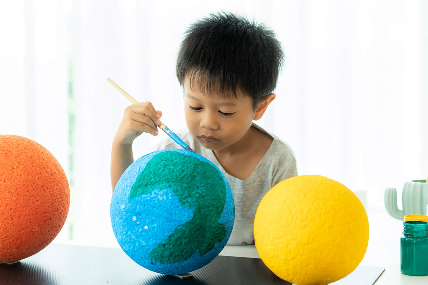 child painting the solar system
