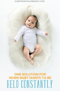 Baby lying down on an infant cushion